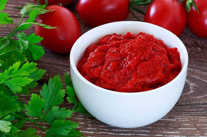 A close up of a white bowl containing freshly made tomato paste, set on a wooden surface, with herbs scattered to the left of the frame.