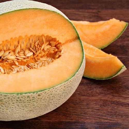 Square closely cropped image of a cut 'Top mark' melon with pale orange flesh, on a brown stained wood surface.