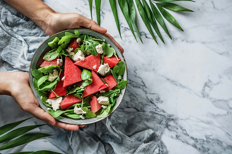 A close up horizontal image of two hands from the left of the frame holding a small ceramic bowl containing a green leaf and melon salad. In the background is a marble surface with foliage scattered around.