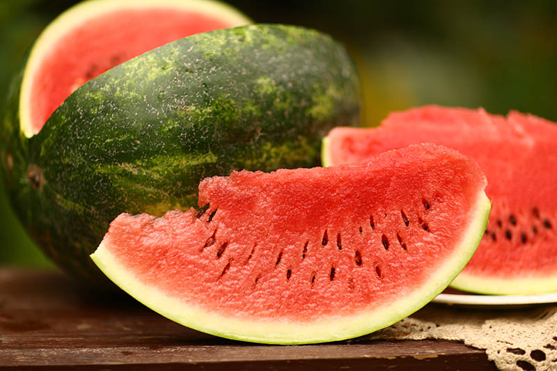 A close up of slices of Citrullus lanatus with dark green skin and bright red flesh, set on a wooden surface, pictured on a soft focus background.