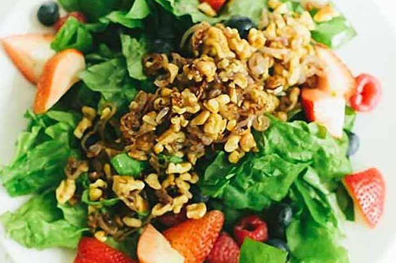 A close up horizontal image of a strawberry, walnut, and olive salad topped with crispy onions.