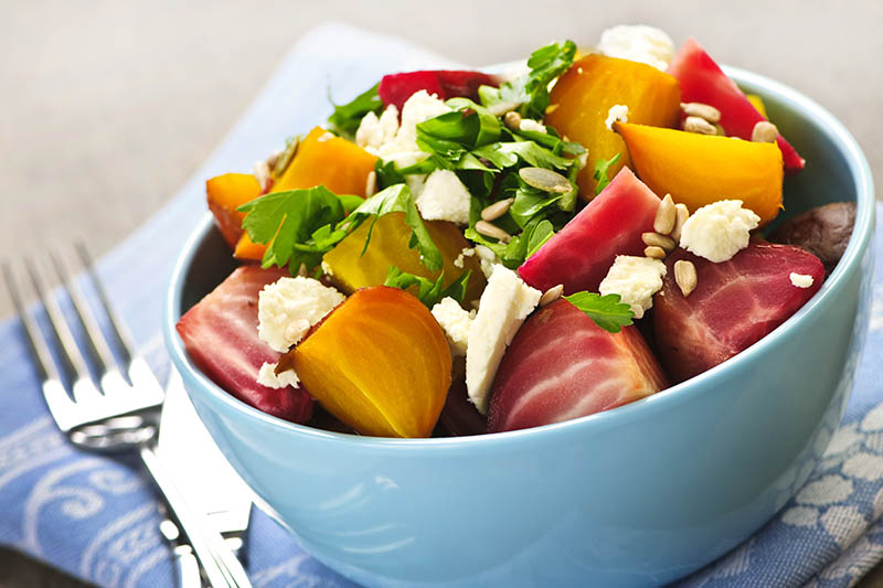 A close up horizontal image of a small ceramic bowl with a colorful salad containing a variety of different colored beets, set on a blue and white cloth, pictured on a soft focus background.