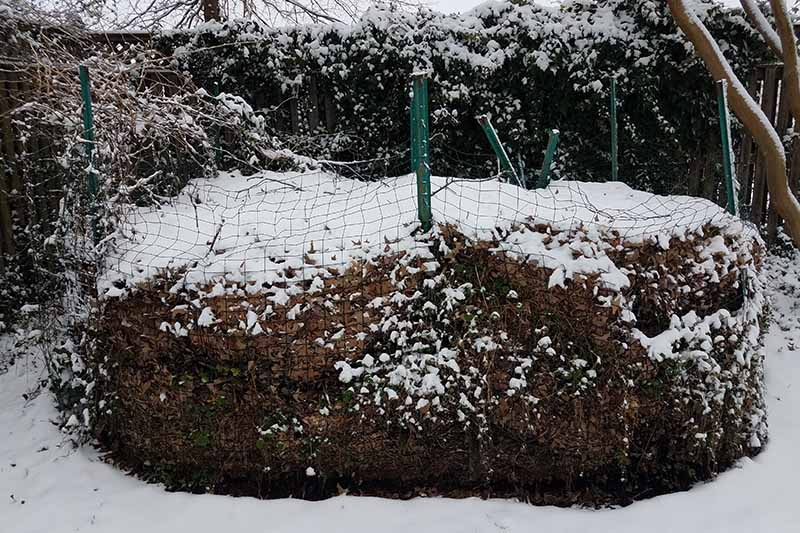 A close up horizontal image of a compost pile in the winter, covered in snow.
