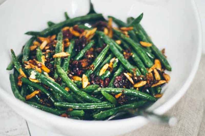 A close up horizontal image of a white ceramic bowl of sauteed green beans set on a wooden surface.