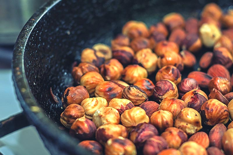 A close up horizontal image of a black pan containing roasted hazelnuts.