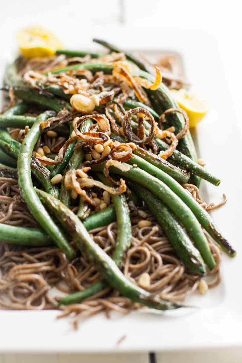 A close up vertical image of a rectangular white plate with a freshly prepared dish of soba noodles with green beans and topped with crispy shallots.