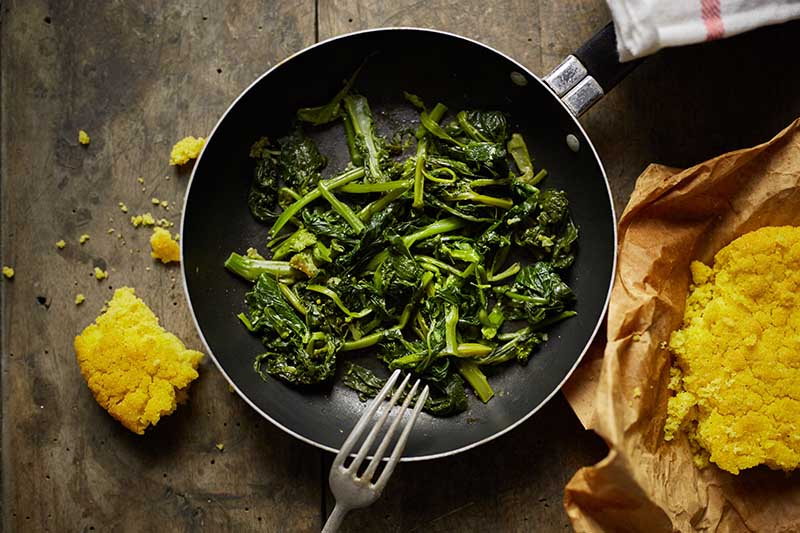 A close up top down horizontal image of a black frying pan with fresh green vegetables, a fork on the side of the pan. To the right and left of the frame is freshly baked cornbread, set on a wooden surface.