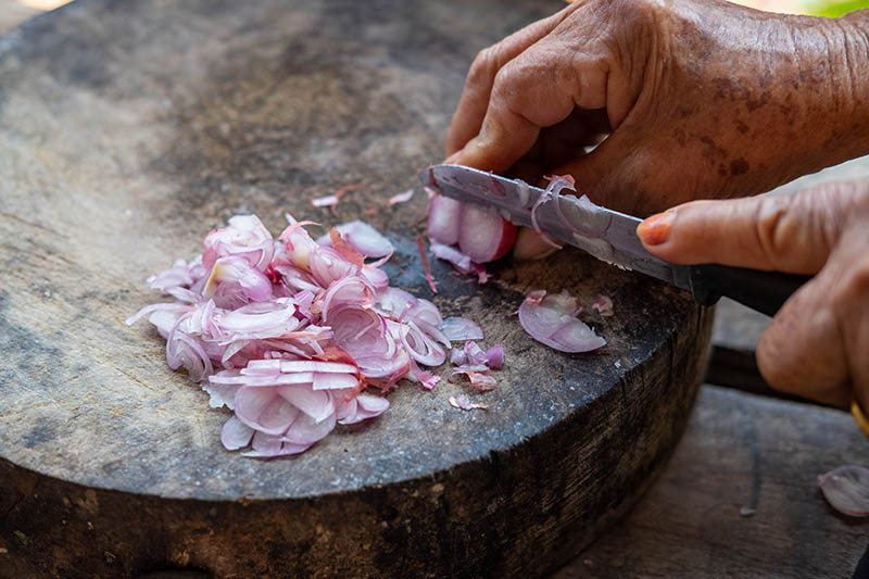 A close up of a hand from the right of the frame slicing a small red shallot on a rustic wooden surface.
