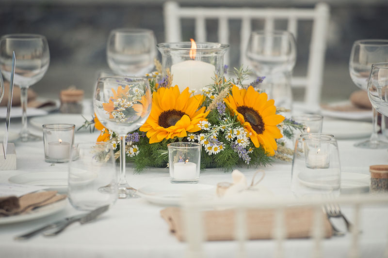 A horizontal image of a floral table arrangement with Helianthus annuus and various other small flowers, surrounded by candles and table settings.