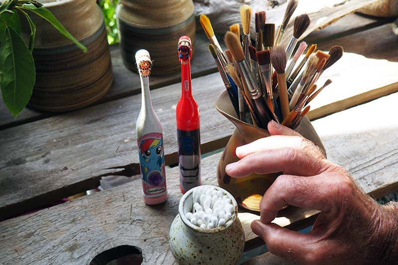 A close up horizontal image of a wooden table with two battery operated toothbrushes, a jar full of art brushes, and a small pot of cotton swabs, with a hand to the right of the frame.