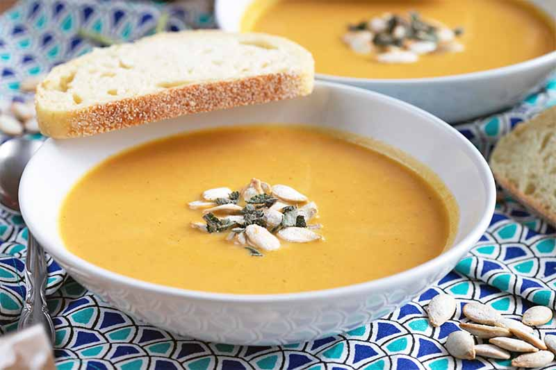 A close up horizontal image of a white bowl of pumpkin soup topped with seeds and a piece of bread on the side, set on a blue fabric, on a soft focus background.