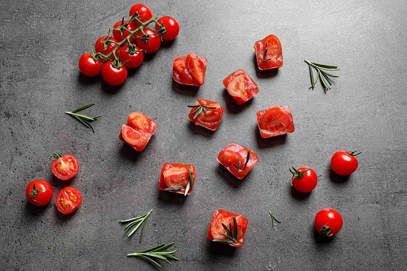 A horizontal image of fresh tomatoes scattered on a gray surface with sprigs of rosemary.