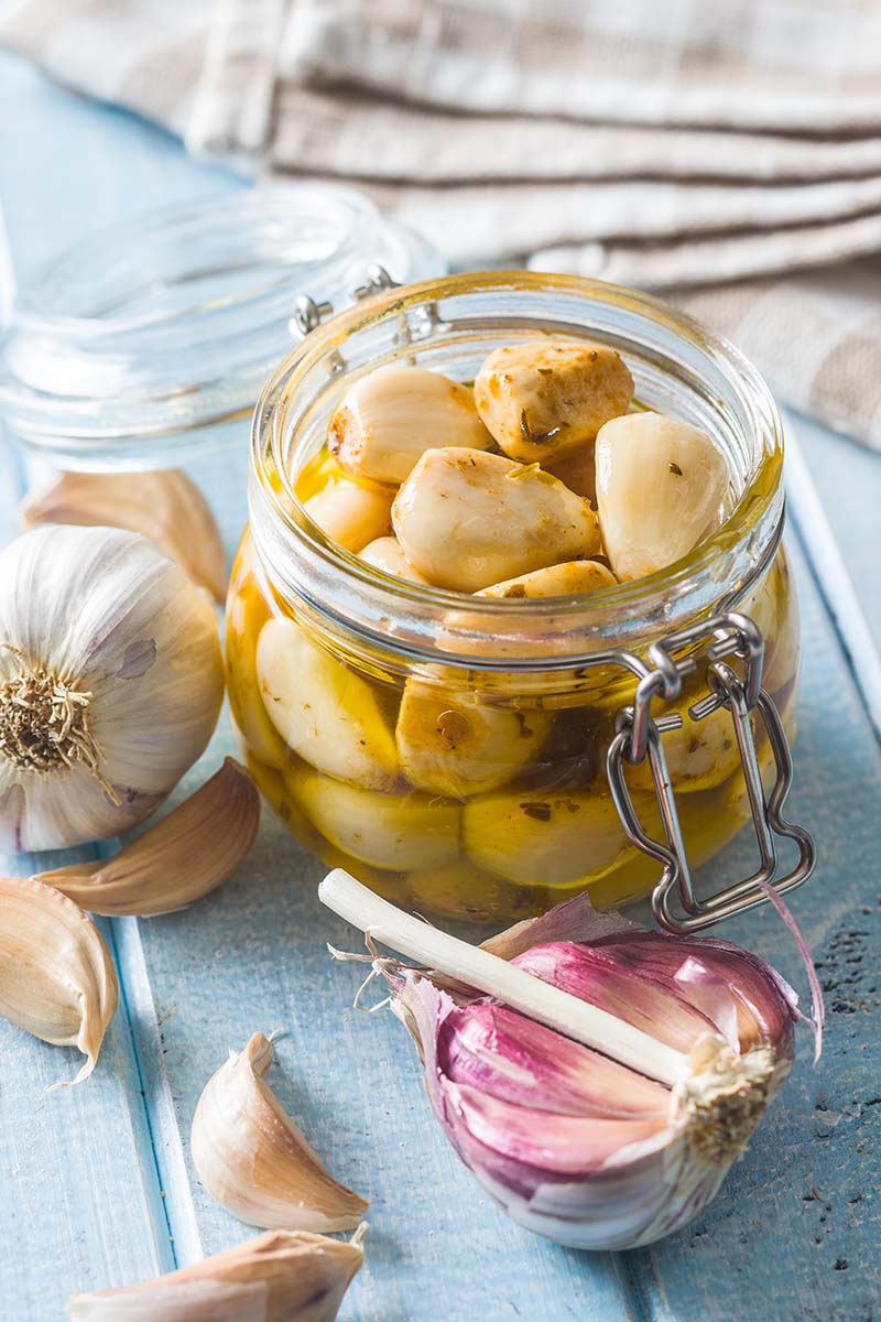 A close up vertical image of a jar of pickles set on a wooden surface with fabric in soft focus in the background.