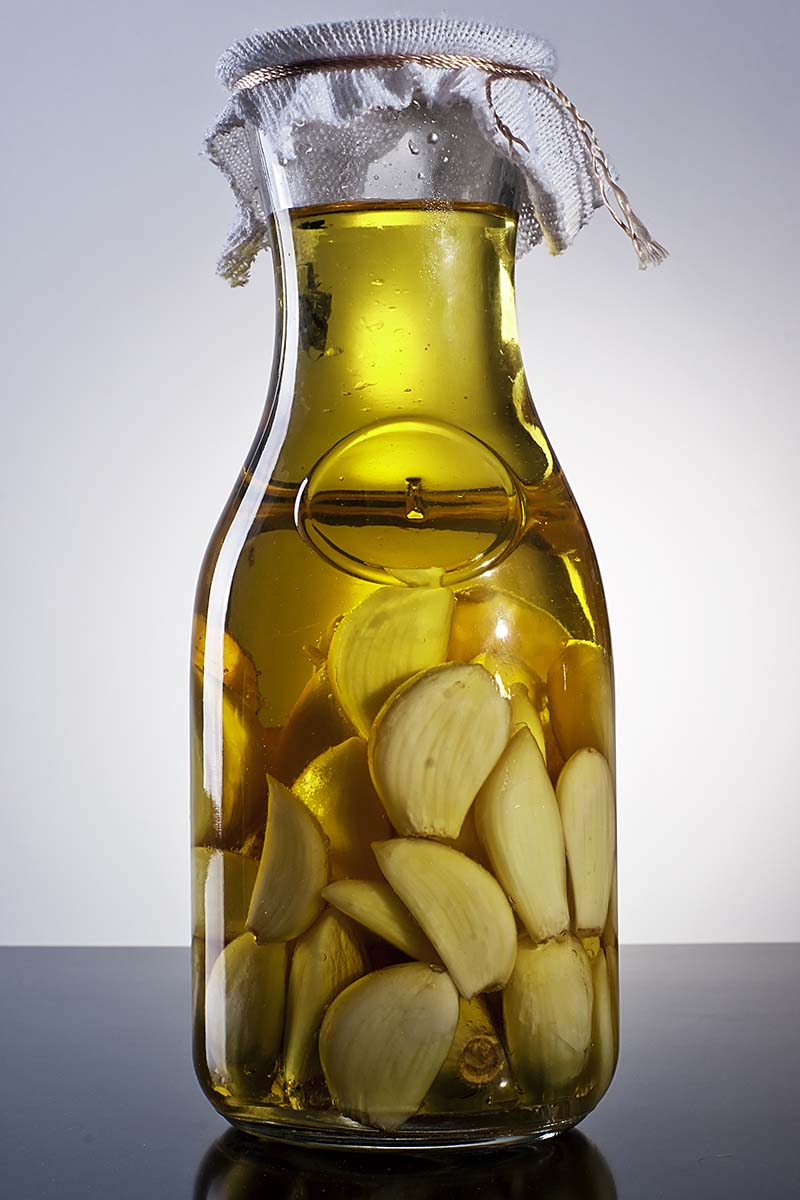 A close up vertical image of a bottle filled with oil and peeled garlic clothes set on a gray surface in front of a white background.