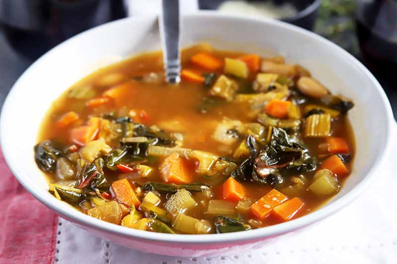A close up horizontal image of a hearty winter soup in a white bowl.
