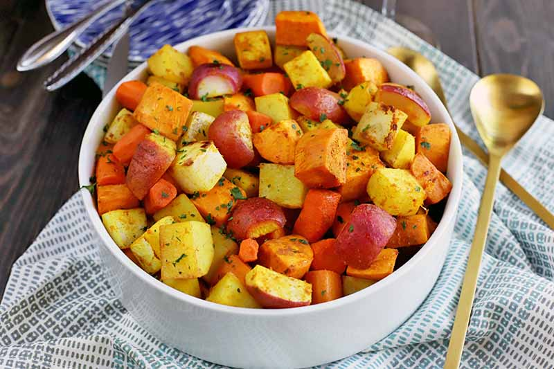 A close up horizontal image of a white bowl containing fresh roasted root vegetables set on a fabric surface.