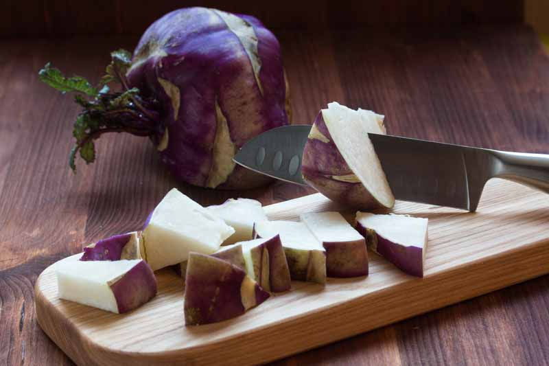 A close up horizontal image of a knife from the right of the frame chopping a purple kohlrabi on a wooden chopping board set on a dark wood countertop.