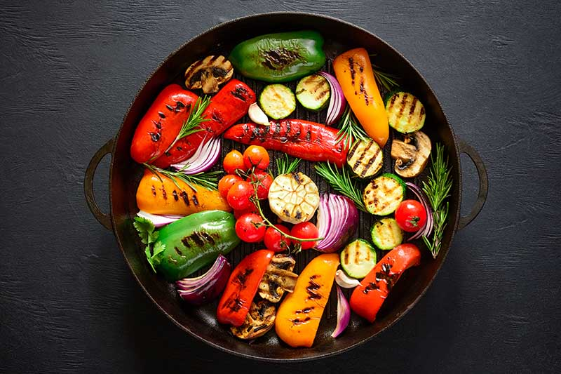 A close up top down horizontal image of a cast iron pan with a selection of roasted vegetables set on a dark gray surface.