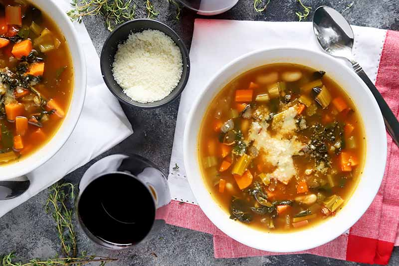 A top down horizontal image of two bowls of winter vegetable soup set on a white and red tablecloth with grated parmesan in the background.