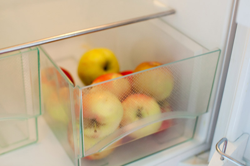 A close up horizontal image of a pile of fresh fruit in the crisper drawer of a refrigerator.