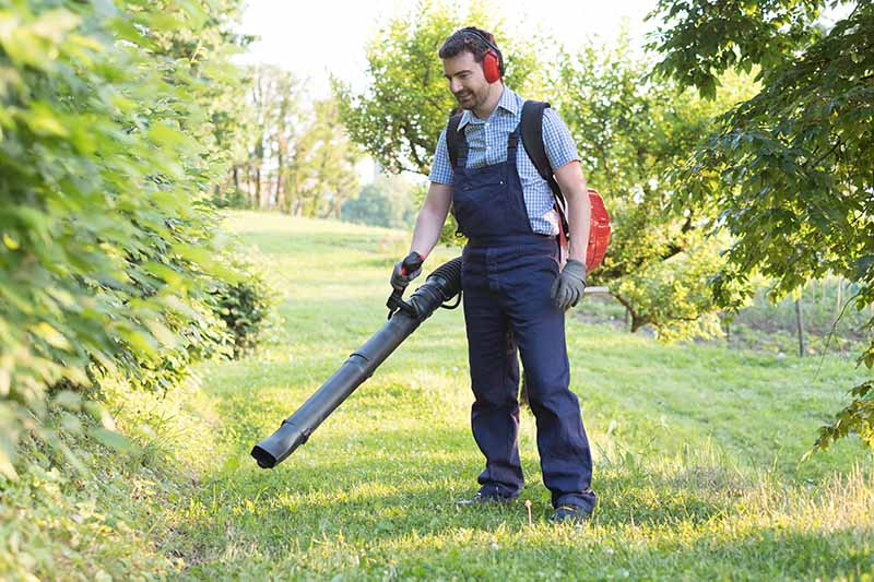 A close up horizontal image of a man using a backpack unit to clean up debris in the garden.