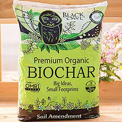 A close up square image of the packaging of Black Owl Organic Biochar set on a wooden surface.
