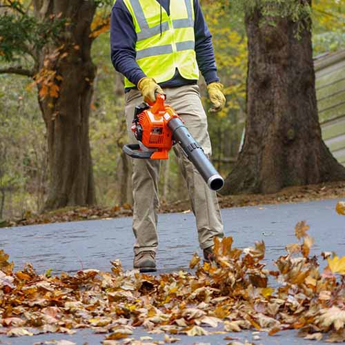A close up of a man using the Echo gas handheld blower to clear up autumn leaves.