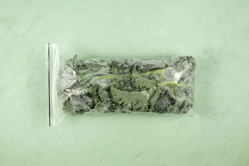 A close up horizontal image of a small plastic bag with frozen leafy greens set on a green surface.