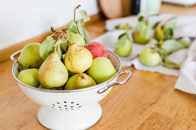 A close up horizontal image of a colander filled with fruit set on a wooden kitchen counter.