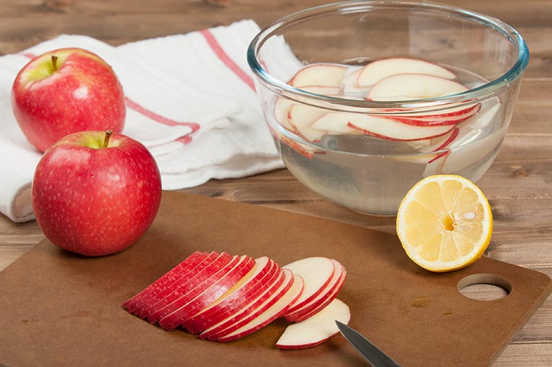 A close up horizontal image of a chopping board with thinly sliced fruit. In the background is a glass bowl with lemon and water to prevent the slices turning brown after processing.