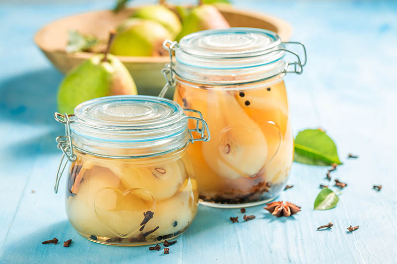 A close up horizontal image of two jars filled with canned fresh pears set on a blue wooden surface with ripe fruits in a wooden bowl in the background.