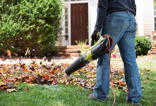A close up of a man using the Ryobi RY42102 to clear up fall leaves.