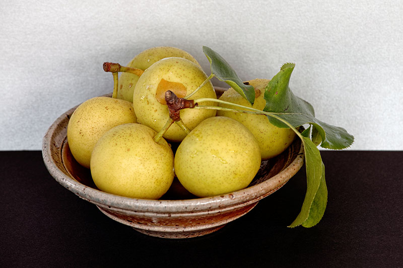 A close up horizontal image of a ceramic bowl filled with freshly harvested Pyrus pyrifolia 'Shinseiki' set on a black surface.