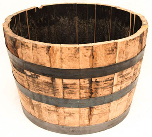 A close up square image of a whiskey barrel planter pictured on a white background.