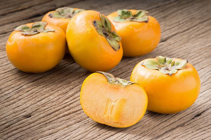 A close up horizontal image of bright orange American persimmons set on a wooden surface, with one cut in half to show the flesh inside.