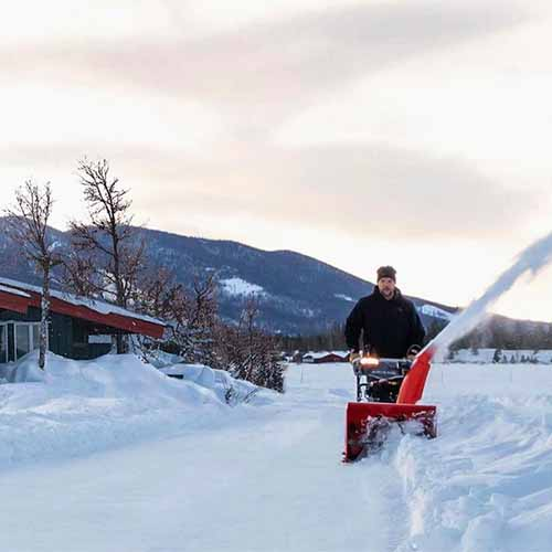 A square image of a man clearing a driveway using the Ariens Deluxe snowblower with a mountain in soft focus in the background.