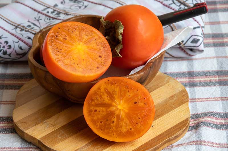 A close up horizontal image of a small wooden bowl with two Asian persimmons, one cut in half set on a fabric tablecloth.