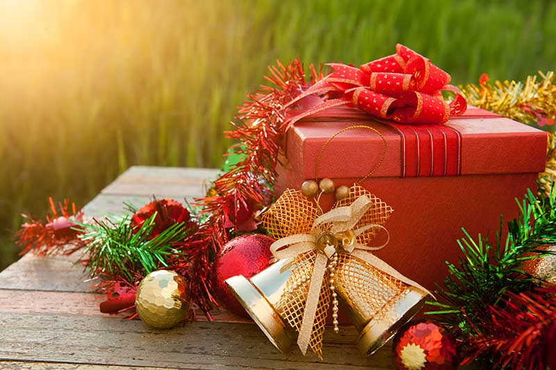 A close up horizontal image of Christmas gifts and decorations set on a wooden outdoor table pictured on a soft focus background.
