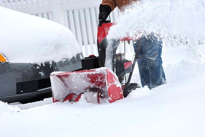 A close up horizontal image of a snowblower clearing a driveway with a car and white fence in soft focus in the background.