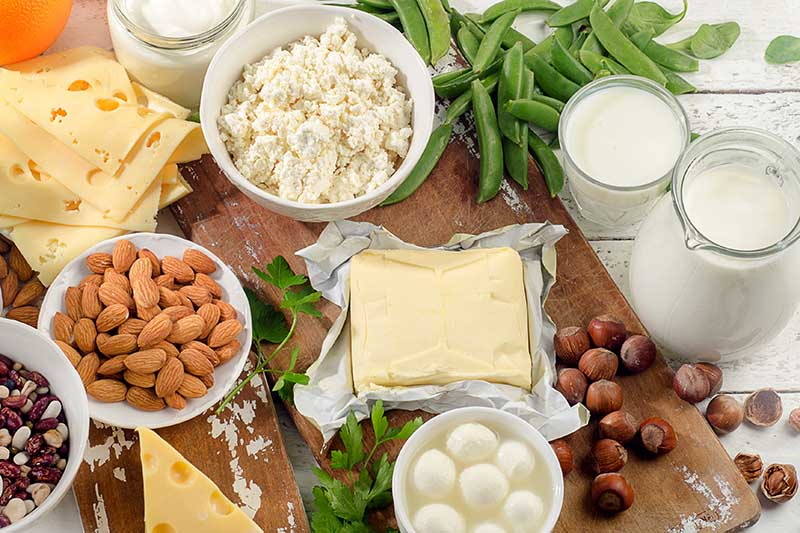 A close up horizontal image of a variety of different foods: nuts, cheese, milk, and vegetables set on a wooden chopping board.