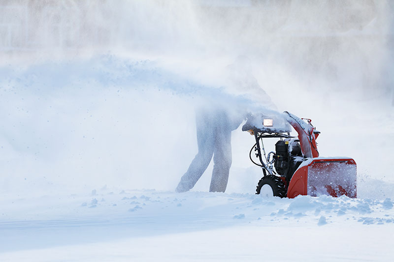 A close up horizontal image of a snowy landscape being cleared with a gas-powered machine pictured on a soft focus background.
