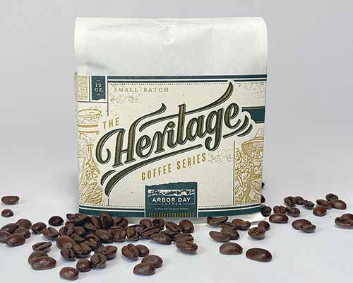 A close up horizontal image of a bag of Heritage coffee with beans scattered in front, set on a white surface.