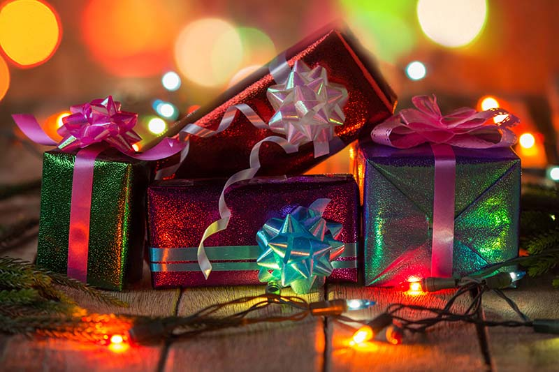 A close up horizontal image of carefully wrapped holiday gifts surrounded by fairy lights and pictured in diffuse light.
