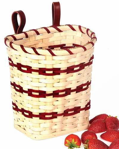 A close up square image of a wicker fruit basket with strawberries to the right of the frame pictured on a white background.
