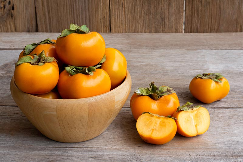 A close up horizontal image of a wooden bowl filled with fresh 'Fuyu' persimmons set on a wooden surface.