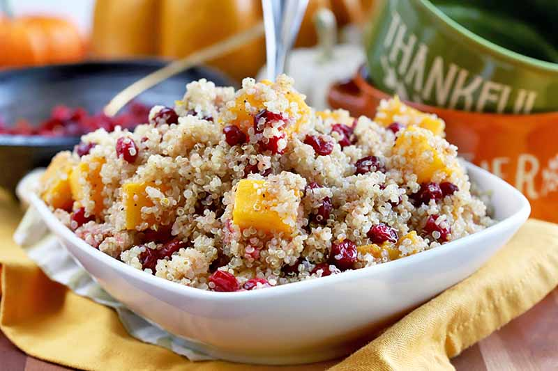A close up horizontal image of a quinoa, butternut, and cranberry side dish in a small white bowl set on a yellow fabric surface.
