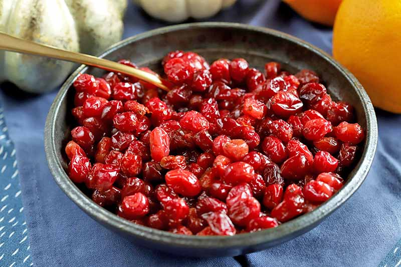 A close up horizontal image of a small dark gray bowl of roasted cranberries set on a blue tablecloth.