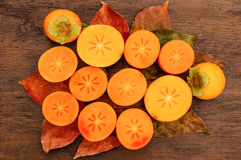 A close up horizontal image of freshly harvested persimmons sliced in half to show the orange flesh inside, set on a wooden surface.