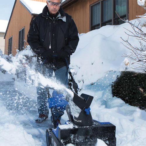 A close up square image of a man clearing a sidewalk using a Snow Joe Ion 18SB with wooden homes in the background.