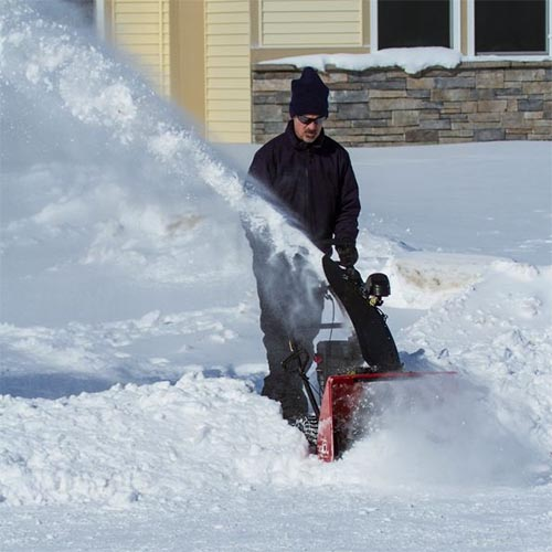A close up square image of a man clearing a pathway with the red and black SnowMaster 824 QXE with a house in the background.